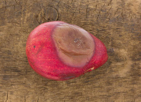 overly: A single rotting red pear atop an old wood board.