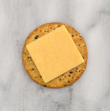 Top view of a square slice of gouda cheese on a multi grain cracker atop a marble cutting board. Imagens
