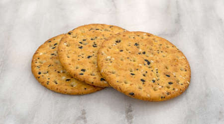 Three round multi grain baked crackers on a gray marble cutting board.