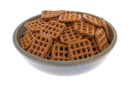 Brown salted waffle pretzels in a stoneware bowl isolated on a white background. Stock Photo