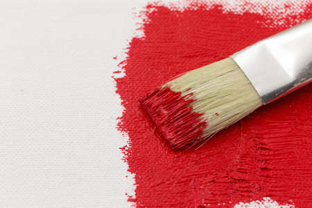 A paintbrush on wet red paint atop a partially painted canvas.