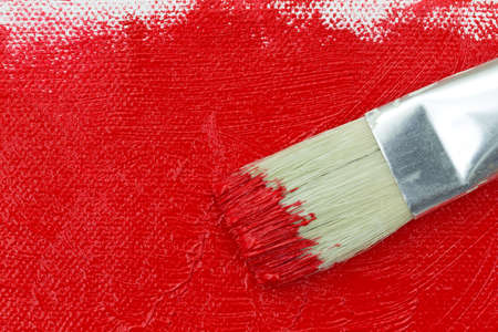 Top view of a paintbrush on wet red paint atop a partially painted canvas. Stock Photo