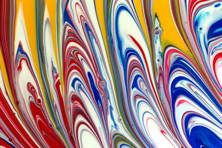 A close view of wet colorful poster paint brushed into an abstract design. Stock Photo