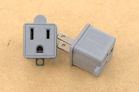 grounding: Two three to two electrical polarized receptacle plug adapters on a pressed board background.