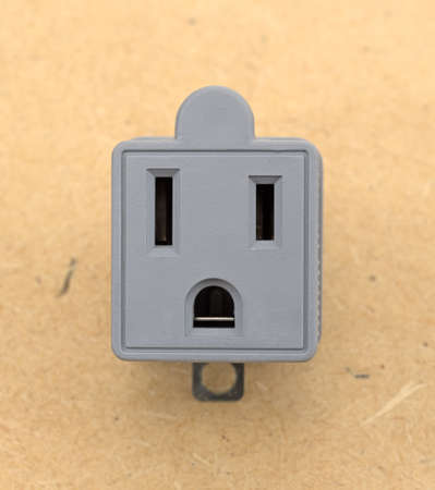 A three to two electrical polarized receptacle plug adapter on a pressed board background.
