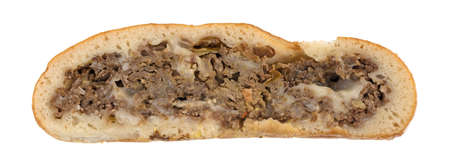 Cut side of a baked steak stromboli isolated on a white background.