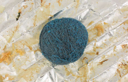 Top view of a stainless steel soap scouring pad atop a greasy tinfoil covering a wire rack. Imagens