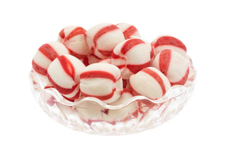 Side view of a glass bowl filled with peppermint balls isolated on a white background.