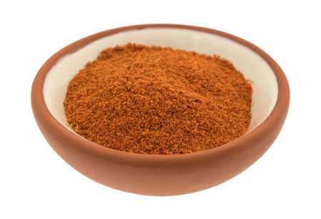 Side view of a small red clay bowl with a portion of taco seasoning isolated on a white background.