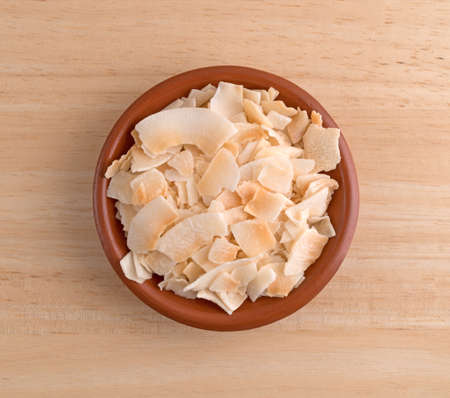 Top view of a small terracotta bowl filled with coconut flakes on a wood table. Stock fotó