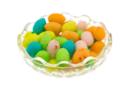 A small glass bowl filled with colorful Easter eggs candy bubble gum isolated on a white background.