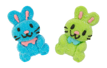 A blue and green marshmallow candy Easter bunny with black whiskers isolated on a white background.
