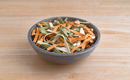 A stoneware bowl filled with vegetable noodles on a wood table.