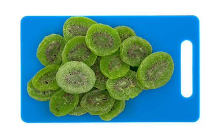 Top view of several slices of glazed kiwi fruit on a blue plastic cutting board isolated on a white background. Stock Photo