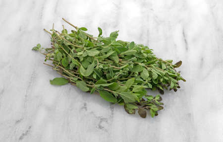 Several branches of organic marjoram on a gray marble cutting board.