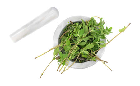 Top view of a portion of organic marjoram to be crushed in a mortar with the pestle to the side isolated on a white background.