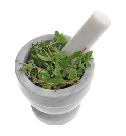 Een gedeelte van organische marjolein die in een mortier en stamper wordt verpletterd die op een witte achtergrond wordt geïsoleerd. Stockfoto