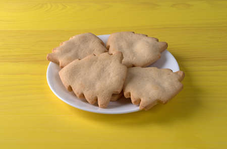 Several freshly baked tree shaped Christmas cookies on a white plate atop a bright yellow wood painted table top.