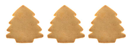 Three tree shaped Christmas cookies in a row isolated on a white background. Stock Photo