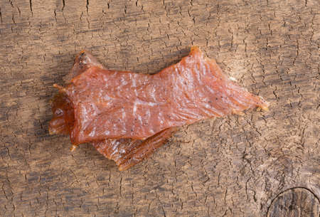 Top view of a two pieces of turkey jerky on an old wood board. Stock Photo