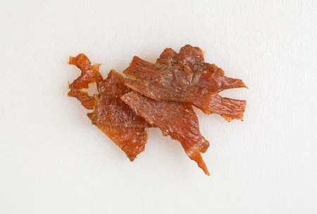 Top view of a several pieces of turkey jerky on a white plastic cutting board. Stock Photo