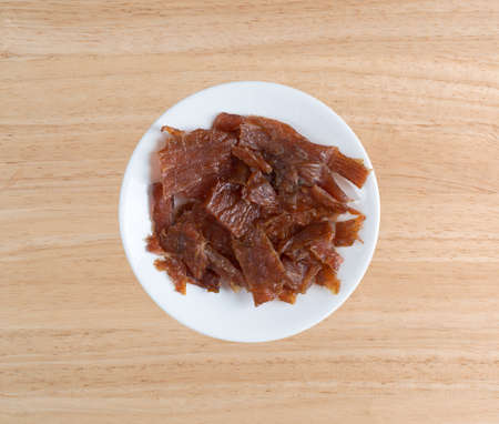 Top view of a turkey jerky pieces on a white plate atop a wood table.