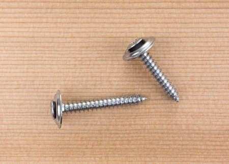 Top view of two stainless steel trim head screws on a wood board. Stock Photo