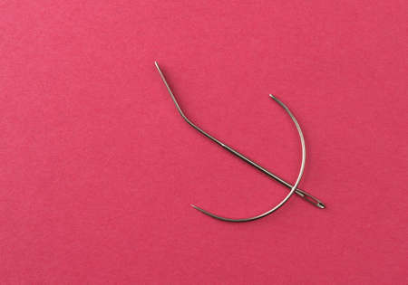 Two heavy duty upholstery cloth needles on a red paper background.