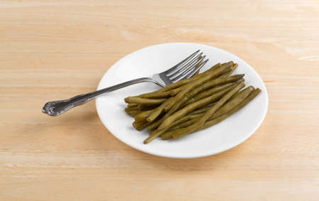 A serving of marinated gourmet green beans on a white plate with a fork atop a wood table top.