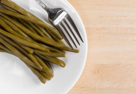 Top close view of a serving of marinated gourmet green beans on a white plate with a fork atop a wood table top.