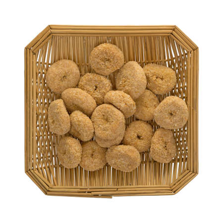 Small bite size caramel flake donuts in a wood wicker basket isolated on a white background.