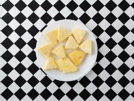Top view of a small white plate with fresh pineapple slices on a black and white checkerboard tablecloth.