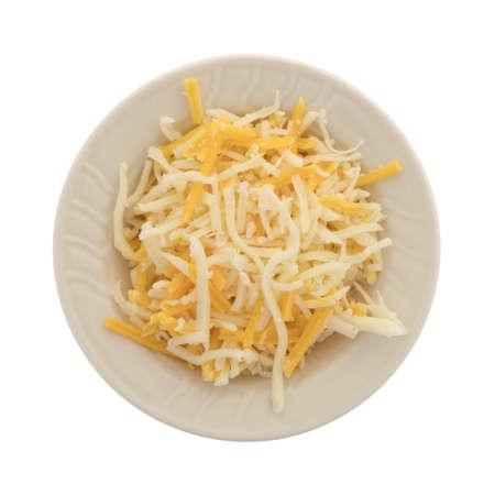 モッツァレラチーズとチェダーチーズのブレンドのトップビューは、白い背景に隔離された小さなボウルにピザトッピング用です。