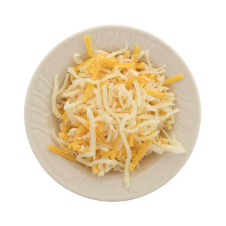 Top view of a blend of mozzarella and cheddar cheeses for pizza topping in a small bowl isolated on a white background.