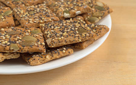 Side view of organic whole wheat seeded crackers on a white plate atop a wood table.
