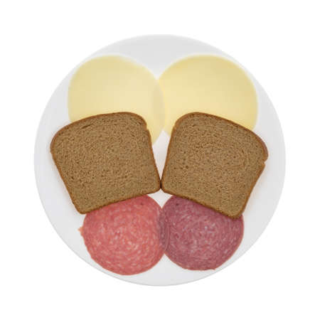 Top view of genoa salami and provolone cheese between stone ground wheat bread slices on a plate isolated on a white background.