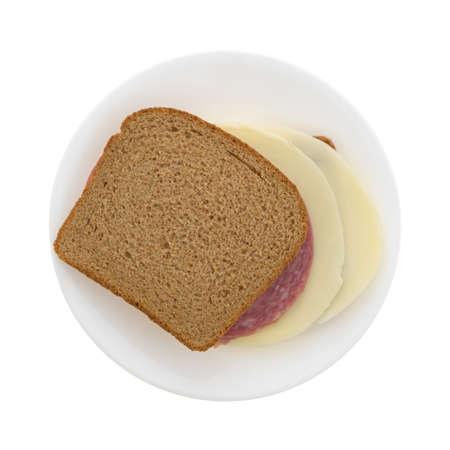 Top view of a provolone cheese and genoa salami on stone ground wheat bread sandwich on a plate isolated on a white background.