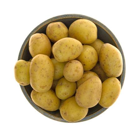 白い背景に隔離された金の赤ちゃんジャガイモで満たされた古いボウルのトップビュー。