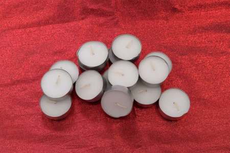 A group of unlit tea light candles on a red cloth background.