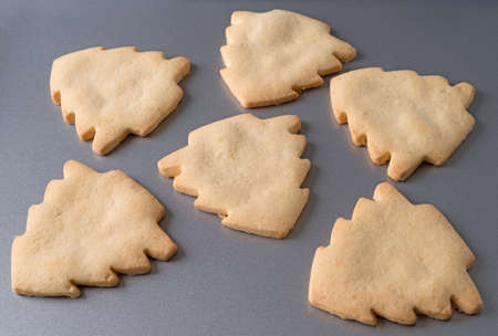 Several freshly baked tree shaped Christmas cookies on a gray metal baking sheet.