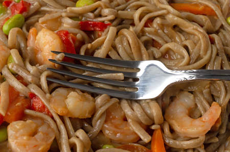 Close view of a shrimp and noodles with vegetables in a ginger sauce TV dinner with a fork on top of the food.