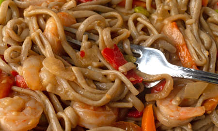 Close view of a shrimp and noodles with vegetables in a ginger sauce TV dinner with a fork in the food.
