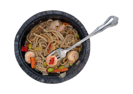 Top view of a shrimp and noodles with vegetables in a ginger sauce TV dinner in a black paper tray with a fork in the food isolated on a white background.