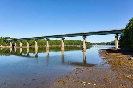 Wide view of the bridge over the Passagassawakeag River in Belfast, Maine on a bright summer day.