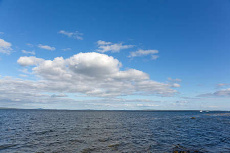 Wide view of clouds above Penobscot Bay in Maine with boats moored in the distance on a summer day.