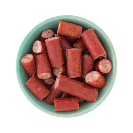 Top view of a green bowl filled with bite size beef sausages isolated on a white background.