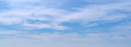 Wide view of white thin clouds against a bright blue sky.