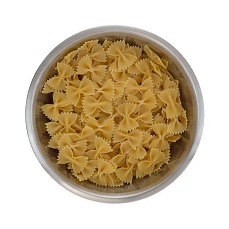 Top view of a metal bowl filled with bow tie pasta isolated on a white background. Stock Photo