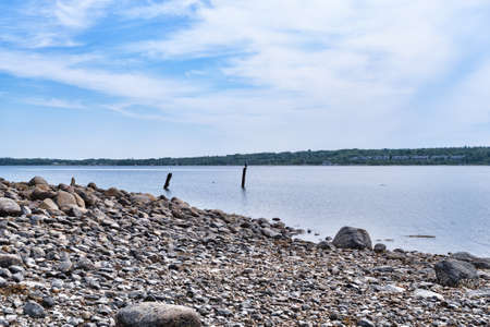 Rocky coastline and Stockton Harbor with two wood posts in the water at Stockton Springs, Maine. Stock Photo