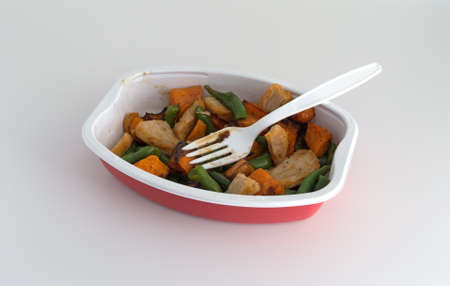 A roasted turkey, sweet potato and green bean TV dinner in a microwavable tray with a plastic fork on a white table top.